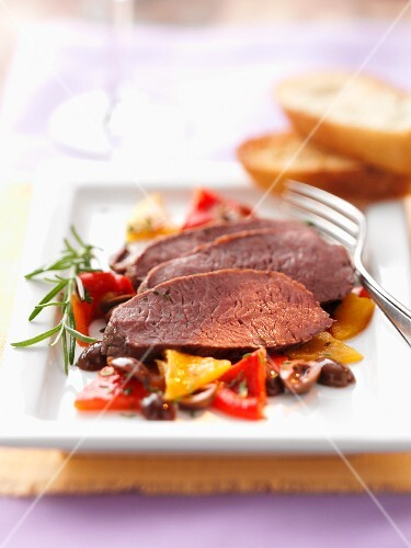 Roast leg of lamb on a bed of rosemary vegetables