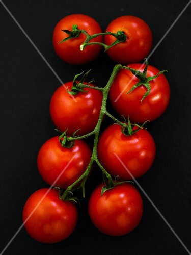 Vine tomatoes on a black surface