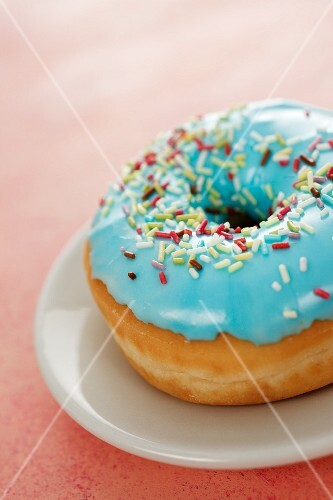 A blue-glazed doughnut decorated with sugar sprinkles
