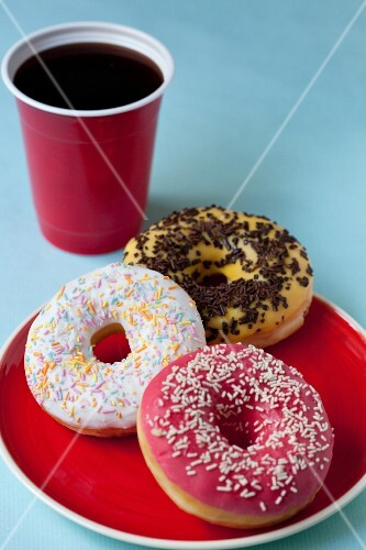 Glazed doughnuts with sugar and chocolate sprinkles and a cup of coffee