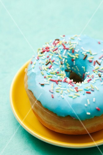 A blue-glazed doughnut decorated with sugar sprinkles