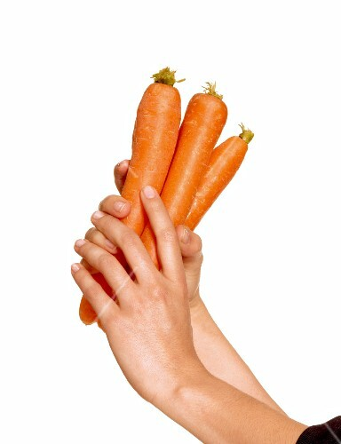 A woman's hands holding three carrots