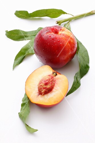 A whole nectarine and half a nectarine with leaves