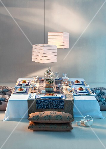 A table laid Asian-style with floor cushions and hanging paper lanterns