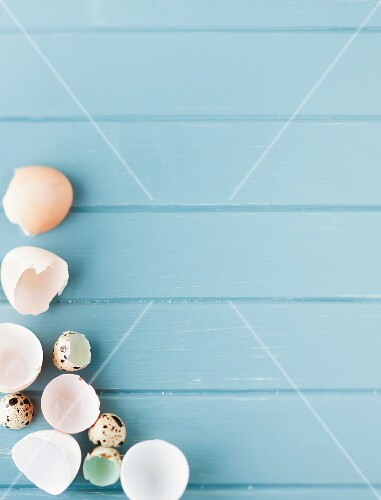 Assorted eggshells on a pale blue painted wooden surface
