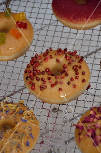Doughnuts with various toppings on a wire rack