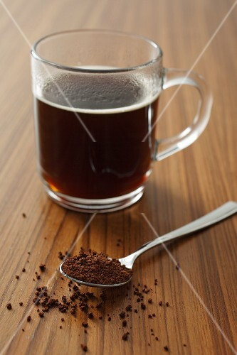 A cup of instant coffee and a spoonful of instant coffee powder