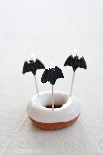 A doughnut with icing sugar and three bat candles
