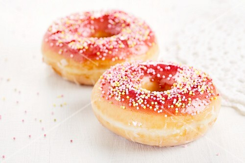 Two doughnuts with a red sugar glaze and sprinkles