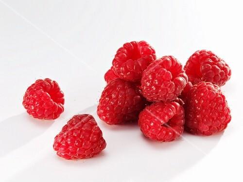 Several raspberries against white background