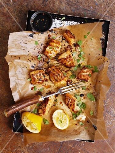 Grilled fish on baking paper on a baking tray (seen from above)
