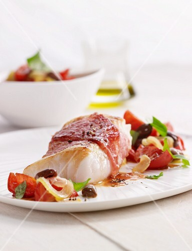 Cod wrapped in ham with a tomato and olive salad