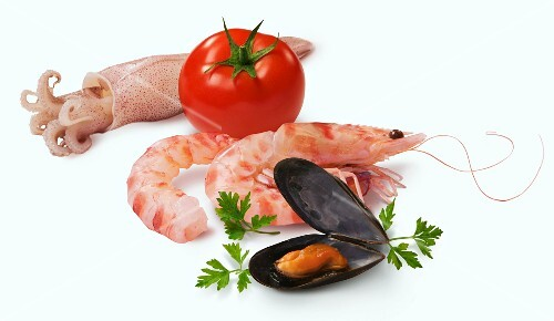 An arrangement of seafood and a tomato