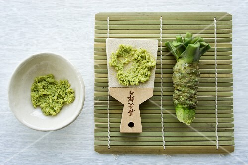 Wasabi root with a traditional grater made of whale skin on a bamboo mat