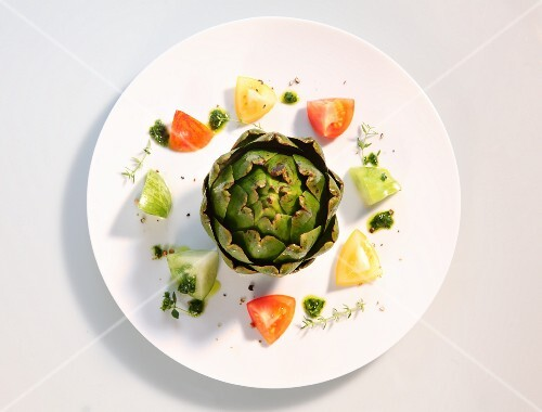 An artichoke with tomatoes and pesto