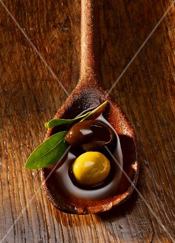 A black and green olive and an olive leaf in olive oil on a wooden spoon