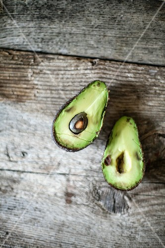 A halved avocado on a wooden surface