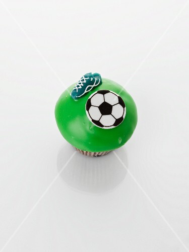 A green cupcake decorated with football motifs