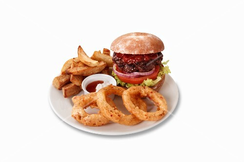 A hamburger with onion rings and chips