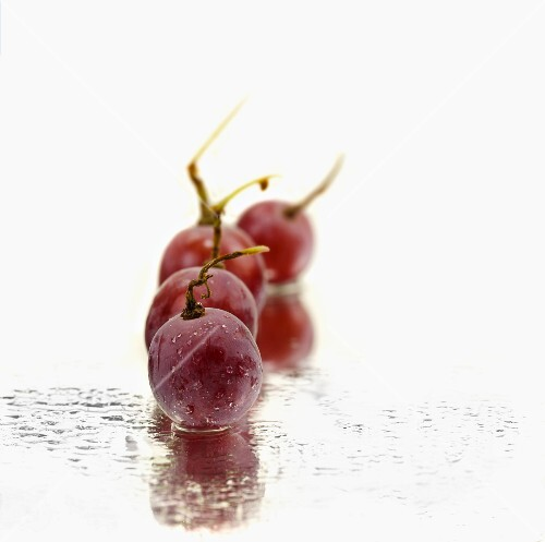 Red grapes on a mirror