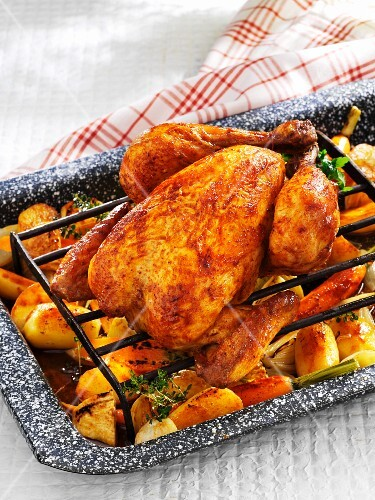 Roast chicken on a bed of oven-roasted vegetables