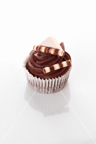 A chocolate cupcake decorated with chocolate sticks