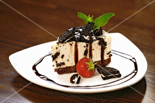 A slice of cheesecake with chocolate biscuits