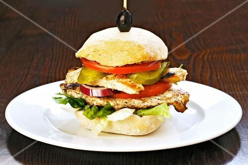 A chicken burger with tomatoes and gherkins