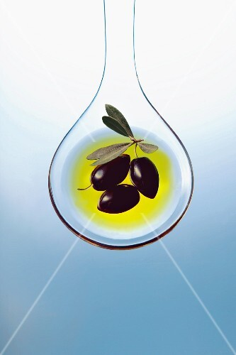 Olive oil and olives on a salad spoon