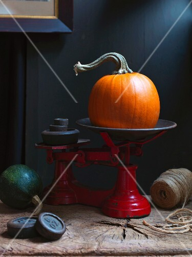 An orange pumpkin on an old pair of scales