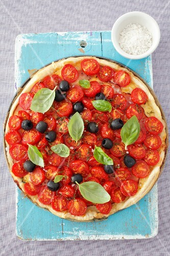 A ham, cheese, cherry tomatoes, olives and basil tart