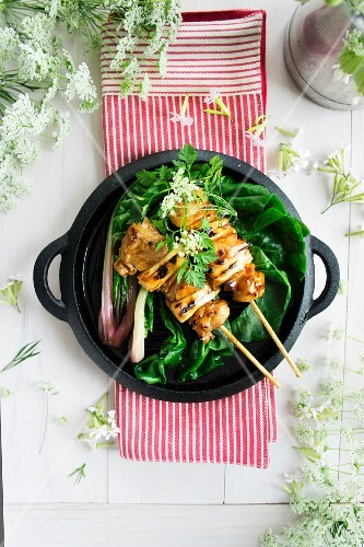 Chicken skewers on a bed of chard