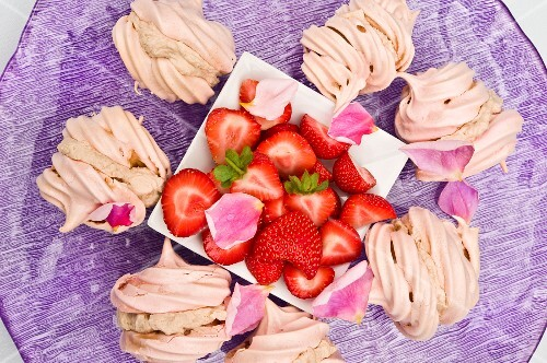 Meringues filled with chestnut cream and fresh strawberries on a purple plate