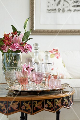 Vase of flowers and various clear and pink crystal glasses on tray on antique, marquetry side table