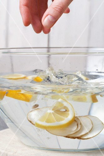 Jerusalem artichoke slices being added to lemon water to prevent browning