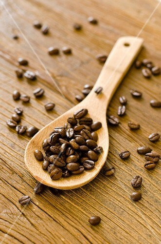 Roasted coffee beans on a wooden spoon and on a wooden surface