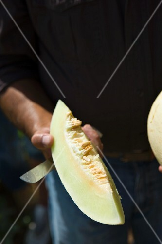 A man holding a melon wedge