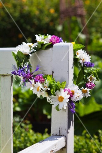 Flower wreath with daisies on a garden bench