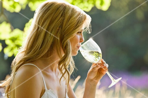 A young woman drinking a glass of white wine