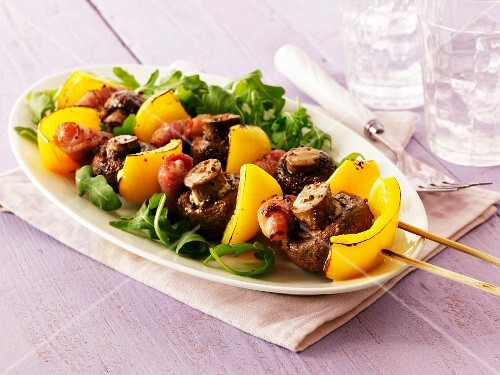 Kebabs with yellow peppers, mushrooms and meat on a bed of rocket on an oval plate