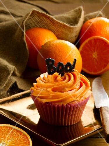 A orange cupcake and fresh oranges