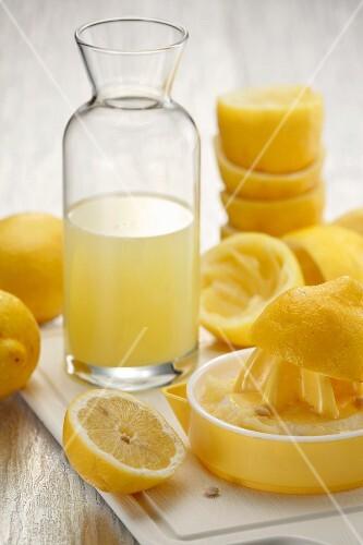 An arrangement of lemon juice, a lemon press and juiced lemons