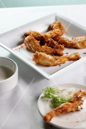Breaded and Fried Frog Legs on a White Plate
