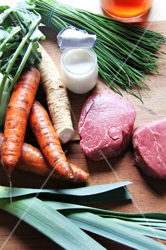 An arrangement of beef, soup vegetables, chives and a pot of cream