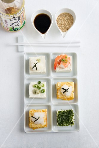 Tofu topped with grated radish, sliced spring onions, a prawn and seaweed