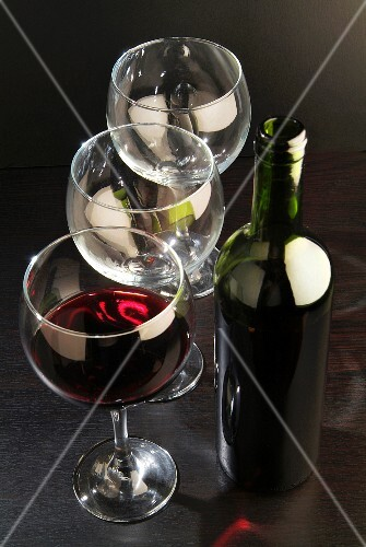 A bottle of red wine, a glass of red wine and empty wine glasses