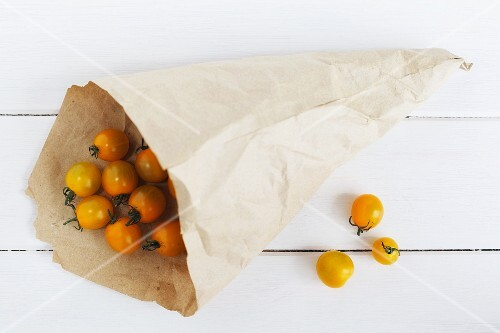 Yellow cherry tomatoes in a paper bag and next to it