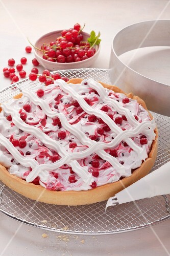 Redcurrant tart with meringue lattice; a cake ring and redcurrants in the background