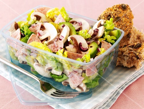 Mixed leaf salad with sausages, mushrooms and avocados in a plastic container
