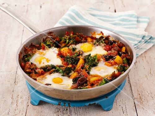 Fried eggs with broccoli and pepper in a pan